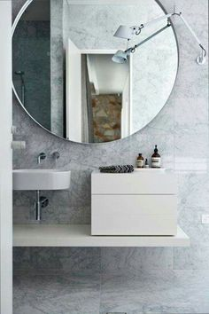 Guest Bathroom Interior. Impressionable mirror against the grey toned tile walls.