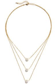 """Even if you're not always immaculate, the Pearl-fectionist Layered Pearl Necklace offers a polished look you can count on! Three layers of dainty gold chain are strung with one faux pearl apiece. Necklace drops 2.5"""" at center, and measures 15"""" around, plus a 2"""" extender chain. Lobster clasp closure. Man made materials."""