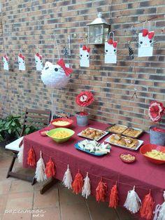 Decoración mesa cumpleaños Hello Kitty, con guirnalda de bolsitas, piñata, centros de flores y guirnalda de flecos creación de http://www.papermoonandco.com