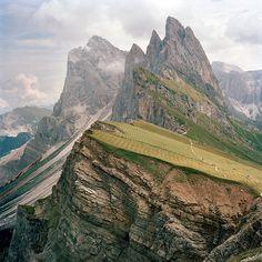 Fotografia diKevin Kunstadt  I picchi seghettati delle Dolomiti svettano su un bucolico pascolo, luogo di sosta per gli escursionisti. Le vette torreggianti della Grande Fermeda (di fronte) e del Sass Rigais (dietro) si innalzano per oltre 2.700 metri.