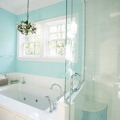 I like the wood paneled drop-in tub next to glass walk-in shower with small corner shower bench tiled in turquoise blue tiles.