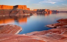 Lake Powell is a reservoir on the Colorado River, straddling the border between Utah and Arizona (most of it, along with Rainbow Bridge, is in Utah). It is the second largest man-made reservoir in maximum water capacity in the United States behind Lake Mead, storing 24,322,000 acre feet (3.0001×1010 m3) of water when full. Current water levels, however, put Lake Powell ahead of Lake Mead in water volume and surface area. Lake Powell was created by the flooding of Glen Canyon by the