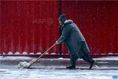CHINA, BEIJING : A worker shovels snow outside a mall during a snowfall  in Beijing on November 22,2015.      AFP PHOTO / WANG ZHAO