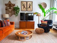 """The room with the orange sofa is their living room, and right away you can see one of the couple's favorite elements: """"All of the windows in the home! We love having plants throughout, so all of the windows are a big help."""""""