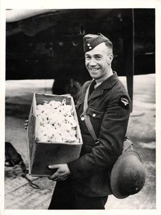 1941- Canadian airman holds a box of tea sacks which were dropped on Holland by the R.A.F.