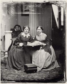 Civil War era two sisters at table, unusual collar and in the background appears to be a dead woman - odd photo....