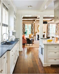 """White kitchen open to living area in """"Boxwood"""", the 1914 Nashville house originally designed by architect Charles Platt and featured in Veranda magazine."""