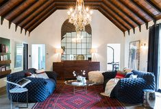Barrel-rolled ceilings with a rather grand chandelier offset the casual beanbag-style sofas in this large living room.