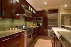 Green Coast granite; walnut shaker cabinets; lighter floor; green glass rectangular tile