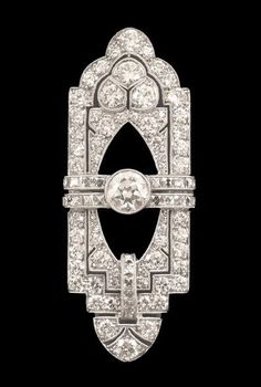 An Art Deco diamond set brooch, by Tiffany & Co. Of pierced asymmetrical rectangular form centred with a circular cut diamond and millegrain set overall with smaller square shaped and circular cut diamonds, in platinum, signed Tiffany & Co.