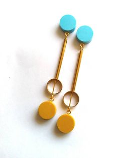 These uber sleek and modern earrings combine deco geometrics and brass with a fresh feminine twist! The mustard and pale blue forms have been hand molded from resin clay and compliment the minimal brass embellishments perfectly. The long stud earrings hang to approx. 9.5 cms from the