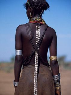 Young Dassanech Girl Wears a Leather Skirt Metal Bracelets Amulets and Bead Necklaces Ethiopia.  by John Warburton-lee