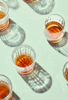Top view of glasses of whiskey or scotch on white background. by Martí Sans - Whiskey, Crystal - Stocksy United Cocktail Photography, Glass Photography, Shadow Photography, Coffee Photography, Photography Portfolio, Still Life Photography, Light Photography, Minimalist Photography, Product Photography