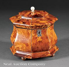 A George III Tortoiseshell Octagonal Tea Caddy, late 18th/early 19th c., with silver handle, line inlay and escutcheon, two covered interior compartments with ivory banding, height 5 1/2 in., width 6 5/8 in., depth 4 1/4 in.