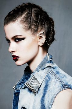 Hair plaited close to head, gothic make up and denim sleeveless shirt with safety pin collar