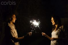 Couple holding sparklers at night