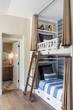 Boys' bunk room with built-in bunk beds accessed by a sliding library style ladder with blue striped upholstered back wall alongside built-in shelves over the headboards with twin beds dressed in striped white and blue bedding topped with gray and navy euro shams finished with gray trimmed burlap grommet bed curtains.