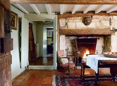 Low ceilings, Rustic Beams, Tile floors & Stone Fireplace with Heavy Mantle..carpets a little old fashioned, i'd swap that for a sheepskin .