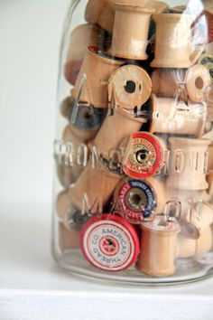 mason jar filled with old spools used as a decorative item in your crafting room