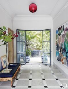A Günther Förg painting hangs in the entrance hall, opposite an 18th-century Swedish bench upholstered in black raffia | archdigest.com