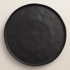 Crafted of stoneware in a sleek, organic shape, our black charger plates feature unique rimmed lips. Layered under other dishes or used as a serving plate, they bring a modern look to your table setting.