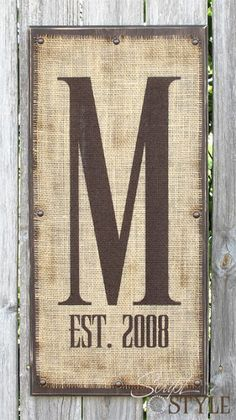 DIY Personalized Monogram Burlap/Wood Sign ~ You could very easily make one for under $5 dollars with a piece of scrap wood, burlap, brown craft paint, a few nails or upholstery tacks and stencils.