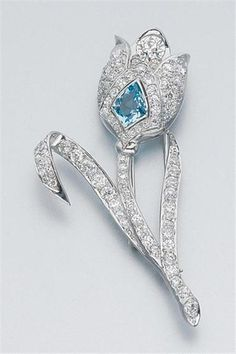 Aquamarine and Diamond Flower Clip-Brooch   Platinum, the stylized tulip centering one shield-cut aquamarine, accented by one old European-cut diamond, approximately .90 ct., set throughout with 87 old-mine cut diamonds, approximately 5.00 cts., approximately 10 dwt.