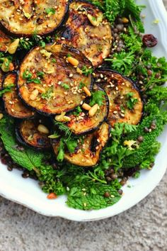 """Eggplant, being a """"meaty"""" vegetable, cooks up beautifully on the grill. Here, eggplant is seasoned up with zesty za'atar and served atop a bed of herbs, pine nuts and beluga lentils."""