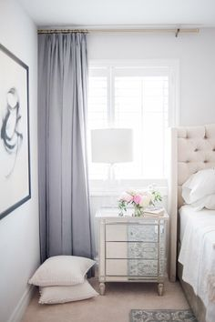 Feminine bedroom with violet curtains, a creme upholstered headboard, and a mirrored vanity