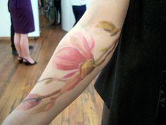 Watercolor flower tattoo on forearm