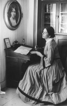 "Louisa Mae Alcott sitting at the desk where she wrote ""Little Women."""