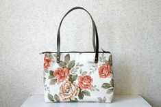 Beautiful everyday medium tote bag made with water resistant cotton canvas. The fabric is printed with beautiful roses. The straps are genuine leather.  The bag closes with a zipper.  The lining is dark brown and it has three pockets inside. Approximate measurements are 11 in high x 14.2