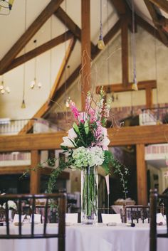 Beautiful pink centerpiece and love the lodge feel at Della Terra Mountain Chateau in Estes Park, Colorado. Get more on weddings in Estes and free assistance in planning your mountain wedding from www.VisitEstesPark.com.   Photography by June Cochran
