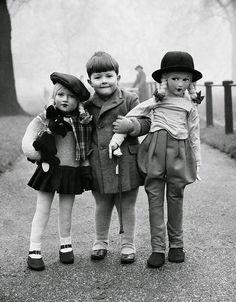 Elliott Erwitt - Boy with two large dolls, 1950s