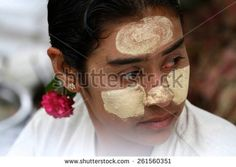 MYITKYINA, MYANMAR - NOVEMBER 6: A close up of a local Burmese food hawker with thanaka on her face at the jetty near the town of Myitkyina, Myanmar on the 6th November, 2012. - stock photo