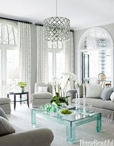 In a Florida house designed by Marshall Watson, a 1980s Lucite-and-glass table provides a jewellike accent to the muted tones of the living room. Asilah chandelier, Jerry Pair.