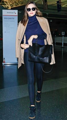 Love Her Outfit: Thanksgiving Travel Edition | Miranda Kerr in black leggings, sneakers, a navy turtleneck and camel coat