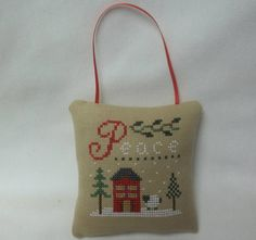 This 4 x 4 ornament with a house and a sheep will be great for your Christmas decor. It is stitched on tea colored evenweave, backed with cotton fabric, and stuffed with polyfil. It has a grosgrain ribbon hanger. Nice for your tree or a knob. Design by Lizzie Kate. Check out more of