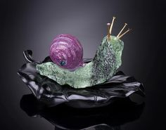 carved snail | Ruby-in-Zoisite Snail on black Obsidian Leaf