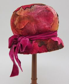 Cloche, USA, 1926. Hat covered in appliqued velvet leaves. The cloche hat has a domed crown completely covered with vari-colored velvet leaves/blossoms in shades of pink, red, green, gold, fuchsia, brown, purple, etc. At base of crown is tied a fuchsia velvet ribbon with bow with ribbons trailing at right. Slight brim below ribbon, which extends downwards. The hat is lined in pink/fuchsia lace, and has an inner purple/mauve grosgrain ribbon hatband inside base of crown.