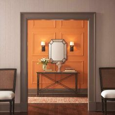 Butterscotch orange paint in the hallway contrasted with dark gray bumps up the drama of classic trim and wall panels. | Photo: Courtesy of Home Depot | thisoldhouse.com