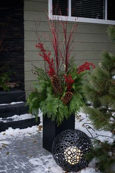 Front Porch Christmas with lights and lantern by pot.
