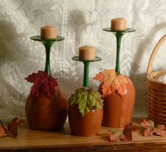 Wine Glass Pumpkin Candle Holders. Wine glasses from the dollar store, acrylic paints, silk leaves and a candle. I could do this!