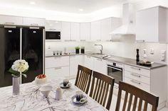 Valkoinen, hyvin valaistu keittiö, valkoisilla kodinkoneilla. #etuovisisustus #keittiö #nelko-keittiöt