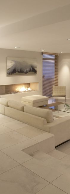Pure white living room with gorgeous lighting and contemporary fireplace. I love a sunken Living room!