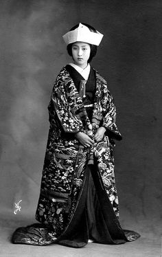"""Bride's Trousseau 1905. A lovely image of a Japanese Bride, wearing a beautiful Uchikake (outer kimono) decorated with a Bamboo, Pine and Plum Blossom motif, known as the """"three friends of winter"""", an auspicious grouping often associated with the marriage ceremony, the motif represents Mount Horai and the wish for a long and happy life for the new couple. S).."""