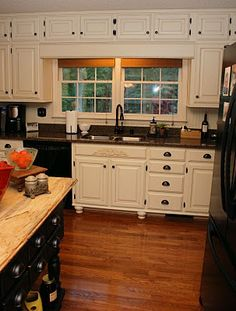 From Oak Kitchen Cabinets to Painted White Cabinets  added feet, dark hinges, dark handles and faucet, added side panels and over the stove piece