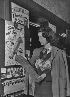 A woman buying a pair of nylons from a street vending machine circa 1950