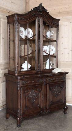 Rendered by talented cabinetmakers from solid French red oak, this handsome vitrine will serve just as well in the library. Featuring finely carved detailing on the cabinet doors, drawers, and framework, its upper glazed tier draws the eye up to the magnificently carved, arched crown. Scrolled legs provide support.