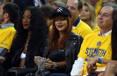 Trading in yellow for black, RiRi cheered on the Cleveland Cavaliers and star LeBron James during Game 1 of the NBA Finals in a Lucid trucker hat and draped leather jacket.   - MarieClaire.com